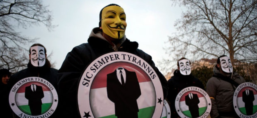 Protestors wearing Guy Fawks masks hold the logos of the international hacker group Anonymous during a demonstration against online censorship laws.
