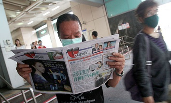"A Taiwanese man wearing a mask reads newspaper titled ""Taiwan has confirmed its first case of H7N9"" at a subway station in Taipei, Taiwan."