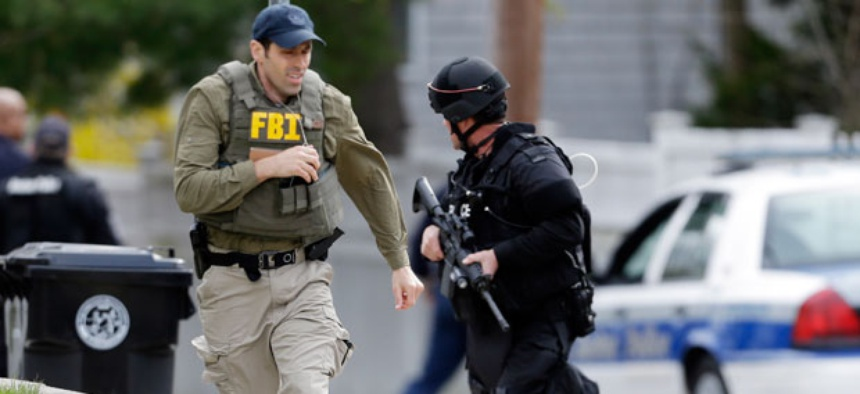 A police officer and an FBI agent search for a suspect in the Boston Marathon bombings April 19.