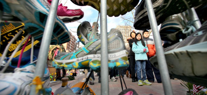 Visitors pause to view a growing collection of running shoes that are part of a makeshift memorial for the victims of the Boston Marathon bombing.