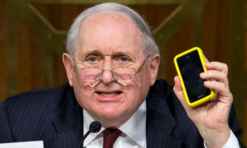 Sen. Carl Levin, D-Mich. holds up his own Apple iPhone while questioning Apple CEO Tim Cook.