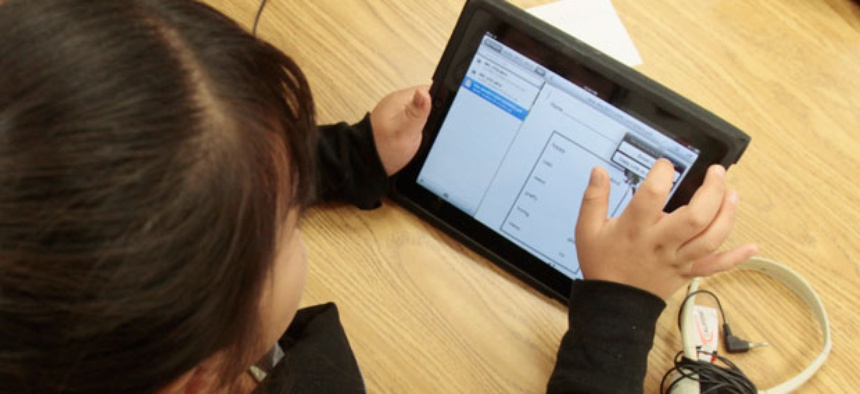 A young girl in a special education classroom reads a worksheet on an iPad in 2011.