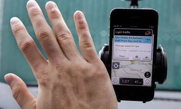 A user waves his hand over traffic and navigation app Waze.
