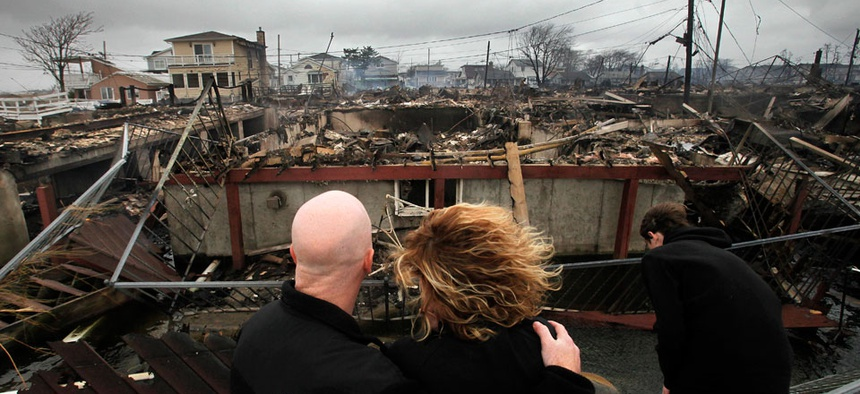 Robert Connolly and his wife Laura embrace has they survey the remains of a home in Breezy Point, New York, following Hurricane Sandy.