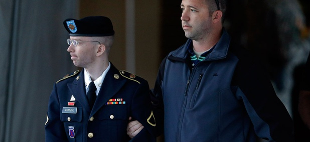 Army Pfc. Bradley Manning is escorted Monday afternoon.