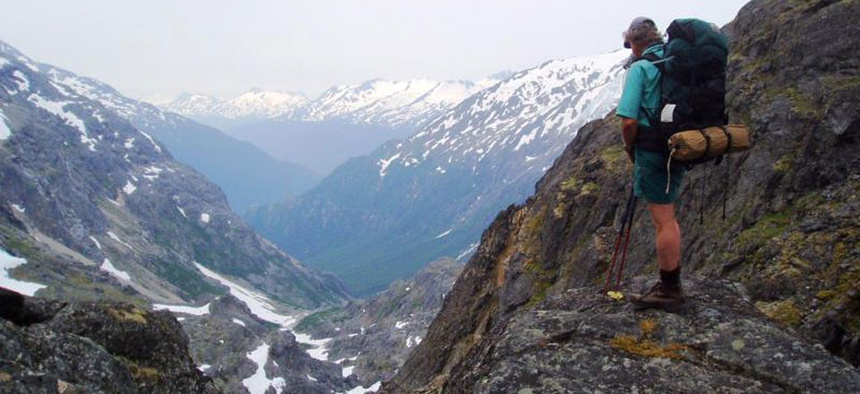 A hiker stands on rock near False Summit looking south at Klondike Gold Rush National Historical Park in Alaska.