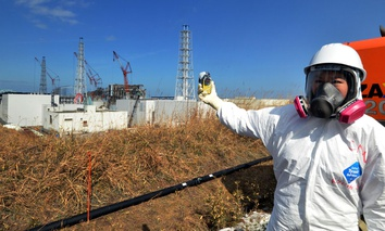 A journalist checks radiation level with her dosimeter near stricken Fukushima Dai-ichi nuclear power plant of Tokyo Electric Power Co.