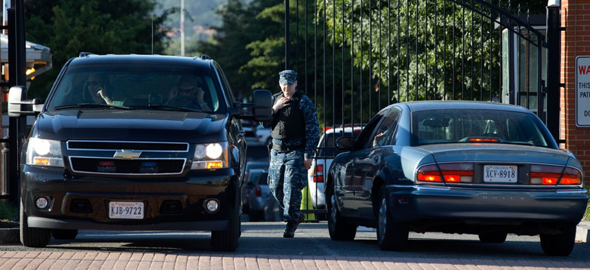 A member of the Navy checks vehicles at a gate to the Washington Navy Yard.
