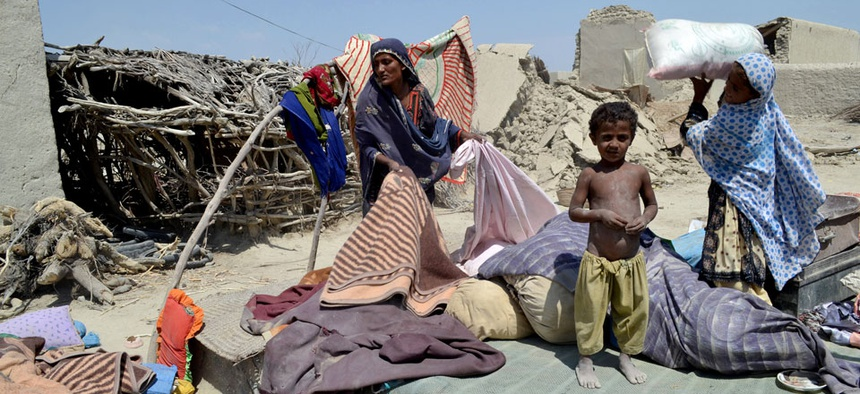 Pakistani villagers collect belongings from their destroyed homes following an earthquake in Labach, Pakistan.