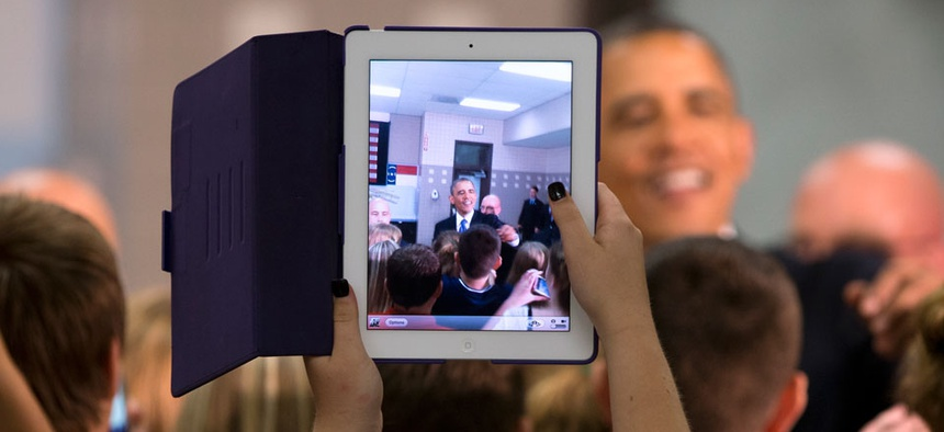 A student uses her iPad to snap a photo of the president in June.