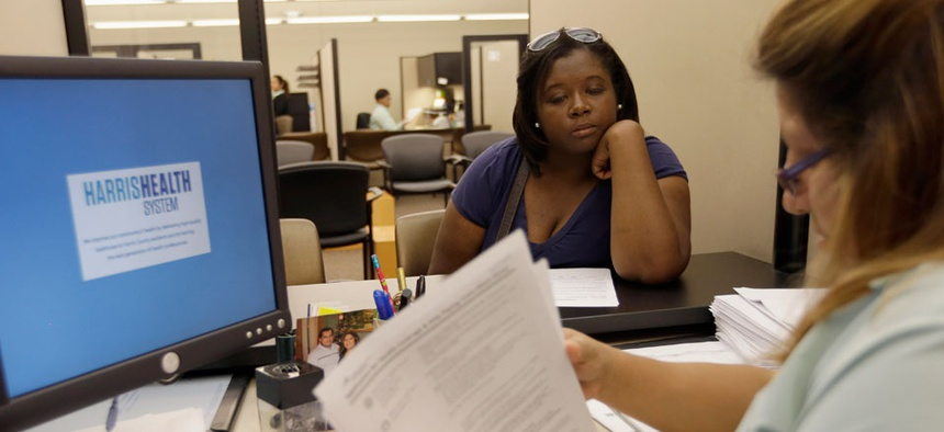 Lillian Ardon, right,  of Harris Health System, helps Vanessa Danielle Cotton, left, with her Affordable Care Act marketplace application on Oct. 1.