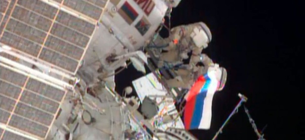 Cosmonauts wave a Russian flag near the end of their spacewalk outside the International Space Station.