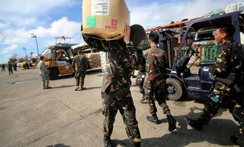 A Philippine soldier carries relief goods delivered in the airport in Tacloban city.