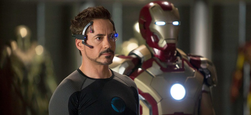 Robert Downey, Jr. as Tony Stark, standing in front of the famed Iron Man suit.