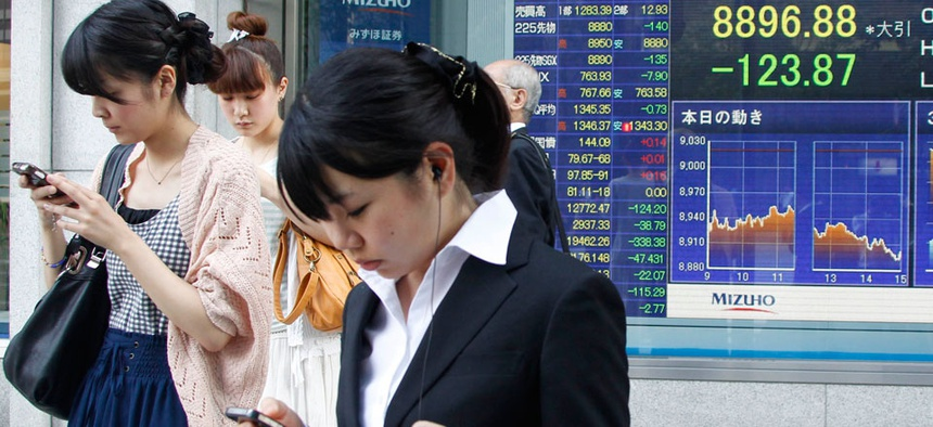 Japanese women operate mobile phones in front of the stock index display of a securities firm in Tokyo.