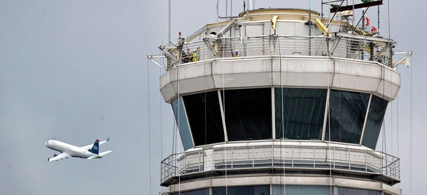 A passenger jet flies past the FAA control tower at Washington's Ronald Reagan National Airport.