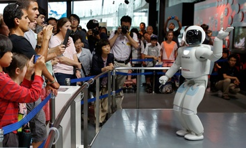 Honda Motor Co.'s interactive robot Asimo gestures while talking with visitors at a demonstration.