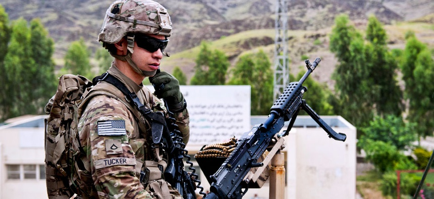 U.S. Army Pfc. Robert Tucker talks on his radio while providing rooftop security for the customs checkpoint at Torkham Gate in Afghanistan's Nangarhar province, April 24, 2013.