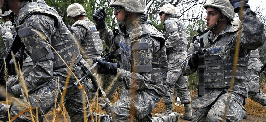 Air Force basic trainees in body armor use hand signals as they take a knee during a tactical drill movement.