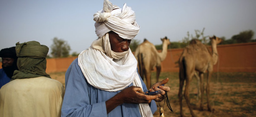 A buyer used two cells phones as he is ready to conclude a deal on a camel at the livestock market in the desert village of Sakabal, Niger.