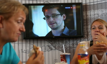 Two passengers eat at a cafe with a TV screen with a news program showing a report on Edward Snowden, at Moscow's Sheremetyevo Airport.