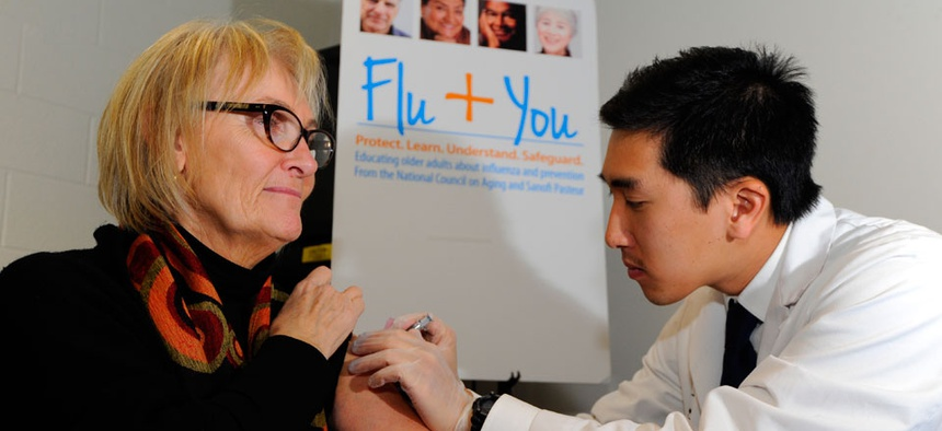 harmacist Jason To gives a flu shot to Diane Marie Dash.