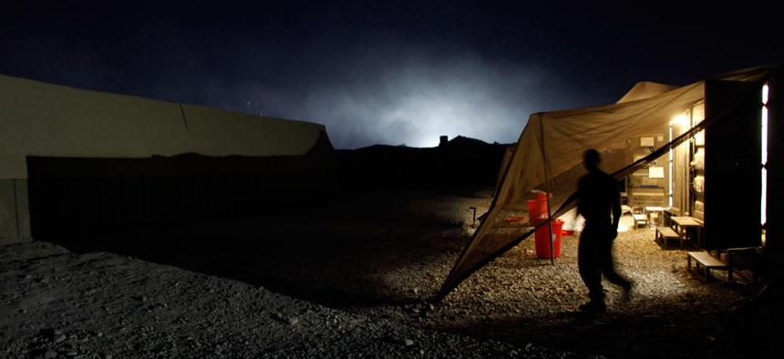 A U.S. Marine exits a steel container, the lights illuminating the smoke from a trash-burning pit, at Forward Operating Base Jackson, in Sangin, Helmand province, Afghanistan.