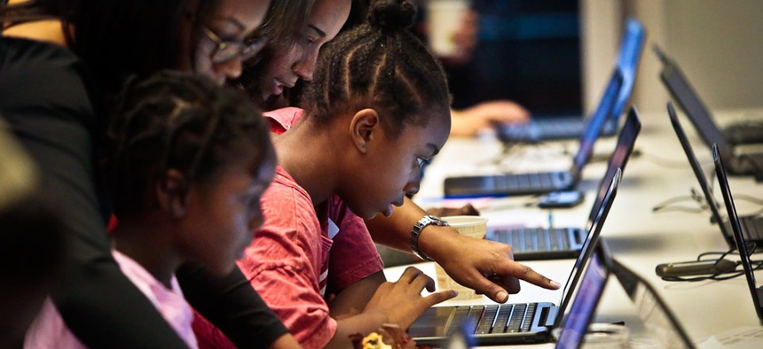 Black Girls Code (BGC) workshop volunteers guide two students during an app building session at Google.