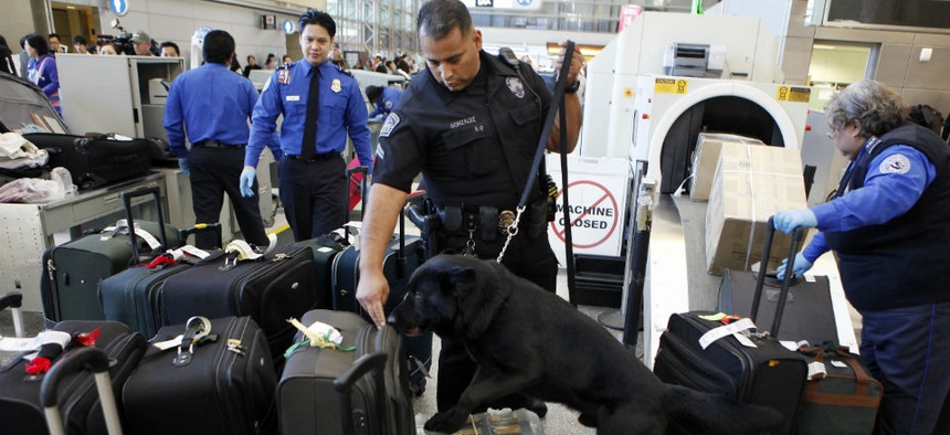 Los Angeles International Airport Enforcement Special Unit police officers use a bomb-sniffing dog to check baggage.