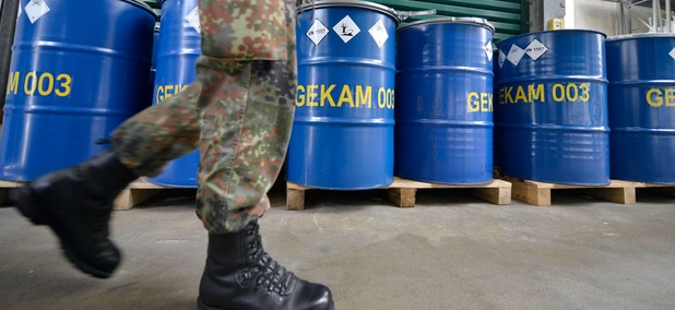 An army officer walks past barrels with chemical waste at the German state-run company GEKA, specialized in the disposal of hazardous materials. The company is tasked to destroy waste material from dismantled Syrian chemical weapons.