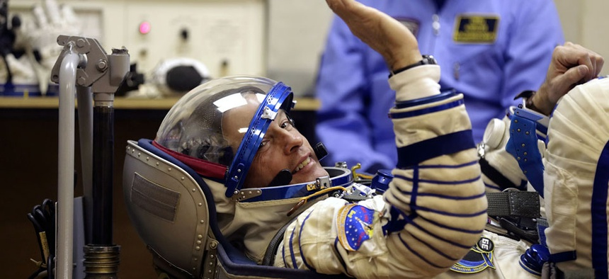 U.S. astronaut Steven Swanson, a crew member of the mission to the ISS, tests a space suit during pre-launch preparations.