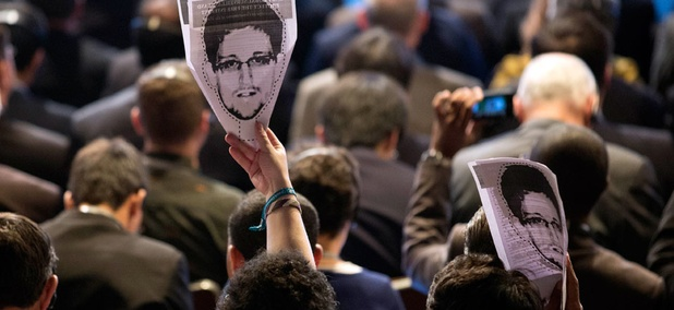 Participants hold up images of former NSA analyst Edward Snowden during the opening ceremony of NETmundial, a major conference on the future of Internet governance in Sao Paulo, Brazil.