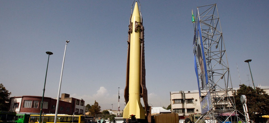 Cars move past a Shahab-3 ballistic missile which is displayed by the Iranian Revolutionary Guard at the Baharestan Square in Tehran.