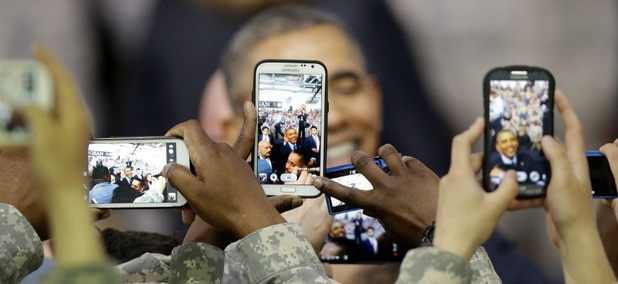 U.S. military soldiers using their smartphones take pictures of President Barack Obama.