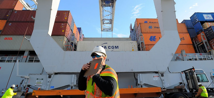 A dock worker communicates on a walkie-talkie while a ship to shore crane loads containers onto a ship at the Georgia Ports Authority Garden City terminal.