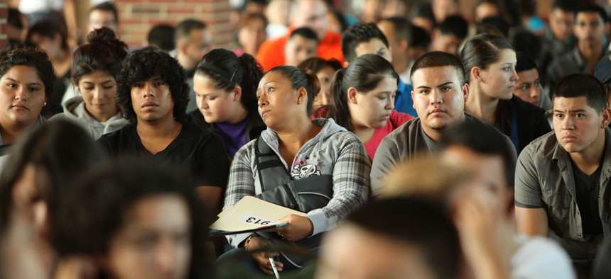 Undocumented people wait to fill out application forms for the Obama administration's Deferred Action for Childhood Arrivals program.