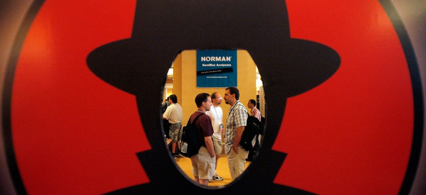Attendees are seen through a Black Hat logo during the Black Hat and Defcon hacker conferences in Las Vegas.