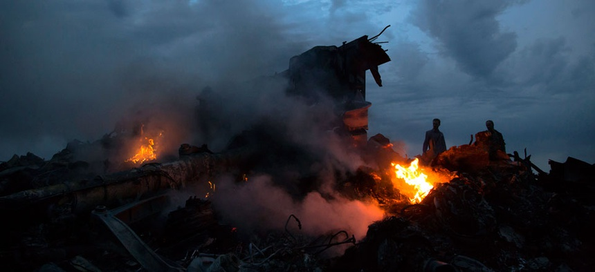 People walking amongst burning debris at the crash site of Malaysia Airlines Flight 17 near the village of Hrabove, eastern Ukraine.