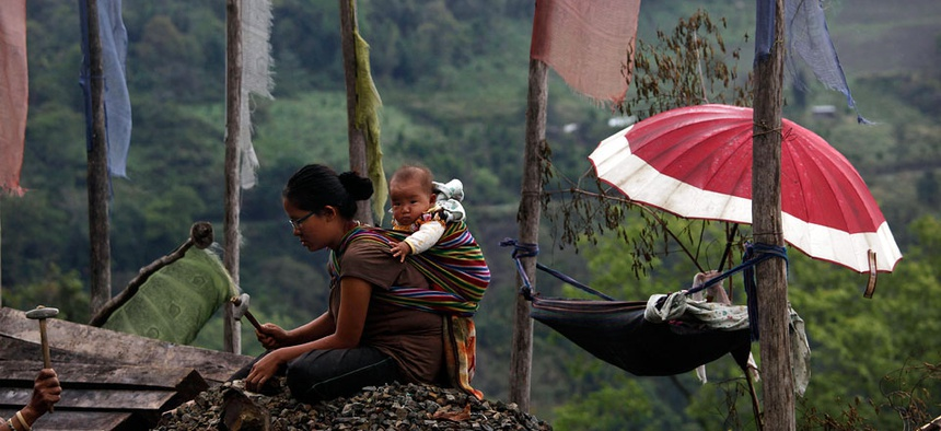 A Bhutanese woman carries her baby on her back as she works on a mountain roadside.