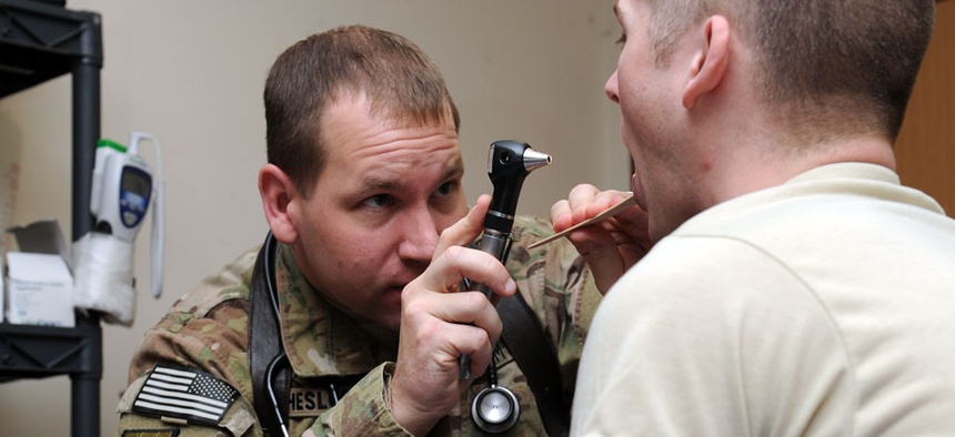 Army Maj. (Dr.) Tim Cheslock examines a patient and fellow soldier at the primary care New Kabul Compound clinic in Afghanistan.