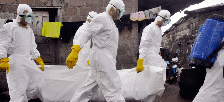 Health workers carry the body of a woman that they suspect died from the Ebola virus.