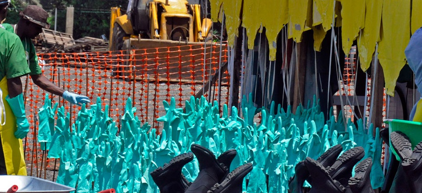 Gloves and rubber boots forming part of the Ebola prevention gear for health workers at a clinic are set outside for the sun to dry them after being washed in Monrovia, Liberia.