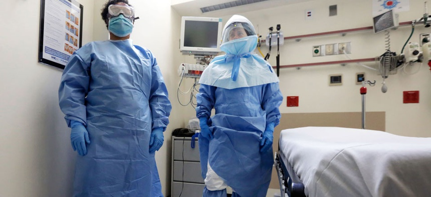 Bellevue Hospital nurse Belkys Fortune, left, and Teressa Celia, Associate Director of Infection Prevention and Control, pose in protective suits in the Emergency Room, during a demonstration of procedures for possible Ebola patients.