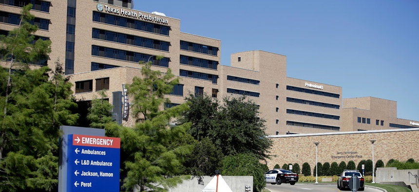 Dallas police vehicles drive toward the emergency room area at Texas Health Presbyterian Hospital Dallas, Thursday, Oct. 16, 2014.