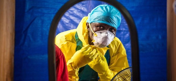 A healthcare worker dons protective gear before entering into an Ebola treatment centre in the west of Freetown, Sierra Leone.