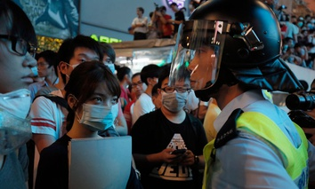 Riot police officers stand guard against protesters at a main road in the Mong Kok district of Hong Kong Friday, Oct. 17, 2014.