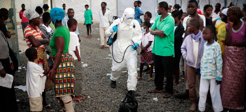 A medical worker sprays people being discharged from the Island Clinic Ebola treatment center in Monrovia, Liberia.