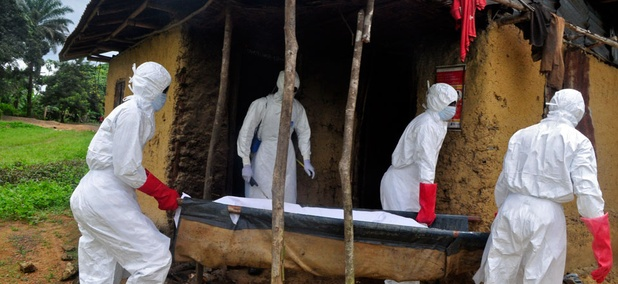 Health workers carry the body of a old man from his house as he is suspected of dying from the Ebola virus in the Siah Town area on the outskirts of Monrovia, Liberia.