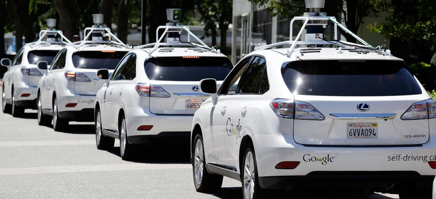 A row of Google self-driving cars are shown outside the Computer History Museum in Mountain View, Calif.