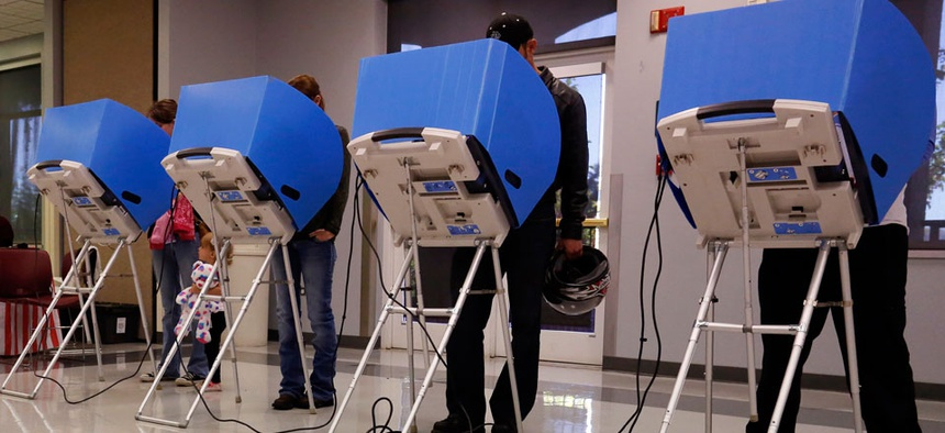 Adams County, Colorado voters casts their vote at a polling place in the Thornton Recreation Center, Tuesday, Nov. 4, 2014.